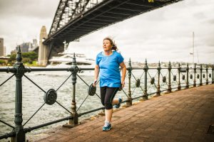 Woman jogging by the bay of Sydney Harbor, Australia