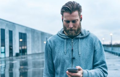 Man wears sports clothes and stands outside. He holds a mobile phone in one hand and looks at the screen. He also wears a headset to hear music or communicate with friends and family while being on the move. The weather is poor and grey.